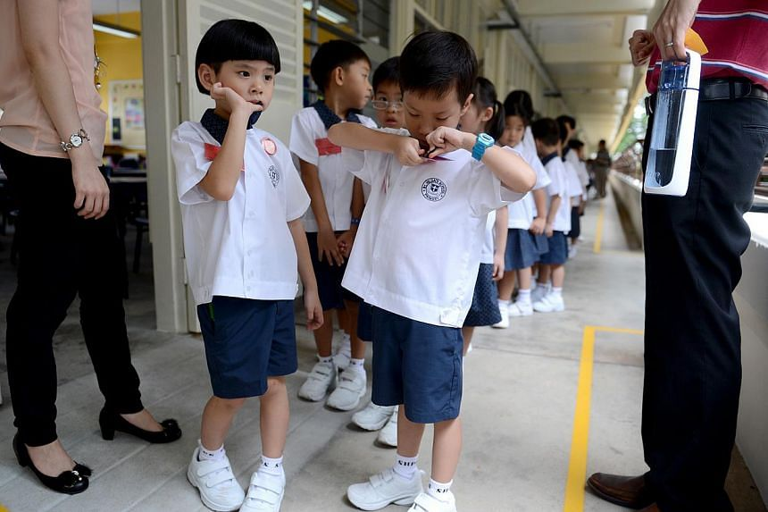 Pupils who are attending Primary 1 at St Hilda's Primary School assemble along the classroom corridor on Jan 2, 2013, the first day of the new school year. Singapore's education system will be continually improved to ensure a person's future is not d