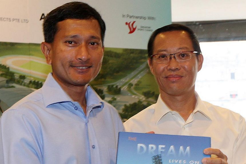 """Dr Vivian Balakrishnan (left), Minister for Community Development, Youth and Sports, receiving a copy of """"The Dream Lives On"""" from Mr Alex Chan, the chairman of the Singapore Sports Council (SSC), on Sept 29, 2010.Mr Chan is a former national s"""