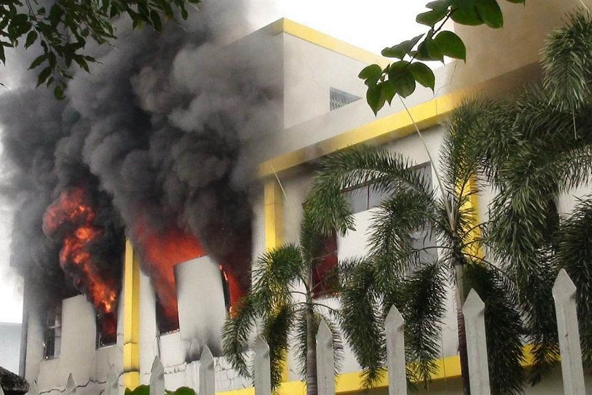 Smoke and flames billow from a factory window in Binh Duong on May 14, 2014, as anti-China protesters set more than a dozen factories on fire in Vietnam, according to state media, in an escalating backlash against Beijing's deployment of an oil rig i