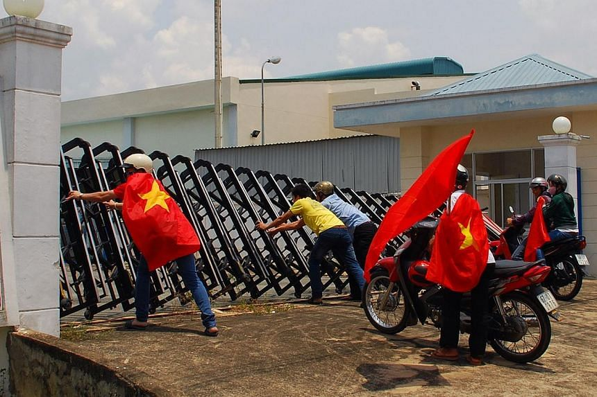 Protesters holding Vietnamese flags attempt to push down the front gate of a factory in Bien Hoa, Dong Nai province, as anti-China demonstrations on May 15 spread to 22 Vietnamese provinces, picture taken on May 14, 2014. Taiwanese workers told of th