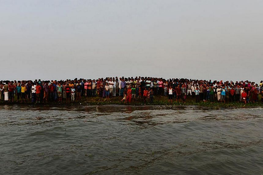 Bangladeshi residents gather near to the site where a ferry capsized and sank in bad weather on the river Meghna in Munshiganj district, some 50km south of the Bangladeshi capital Dhaka on May 15, 2014. A heavily-laden ferry capsized and sank in cent