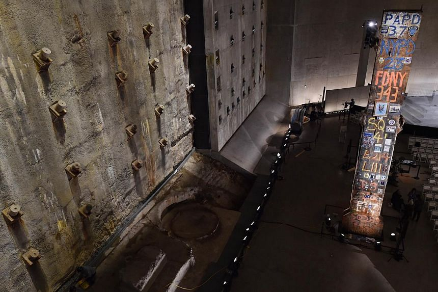 The symbolic Last Column (right), a steel beam from one of the World Trade Center towers, stands near the Slurry Wall (left), which holds back the Hudson River waters, seen during a press preview of the National September 11 Memorial Museum at the Wo