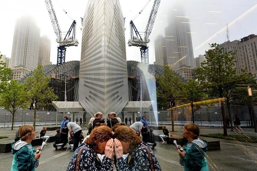 People try to look through the windows of the National September 11 Memorial Museum during the museum's dedication ceremony in New York on May 15, 2014. -- PHOTO: AFP