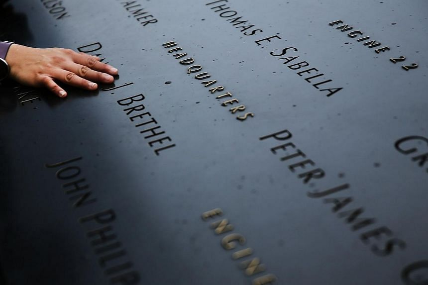 A woman places a hand on the names engraved along the South reflecting pool at the Ground Zero memorial site during the dedication ceremony of the National September 11 Memorial Museum in New York on May 15, 2014. -- PHOTO: AFP