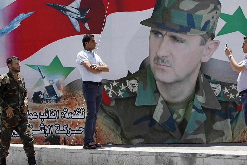 A man takes a photo of his friend in front of a poster of Syria's President Bashar al-Assad at Umayyad Square in Damascus on May 16, 2014. The UN Security Council is expected to vote Thursday on a resolution to haul Syria before the International Cri