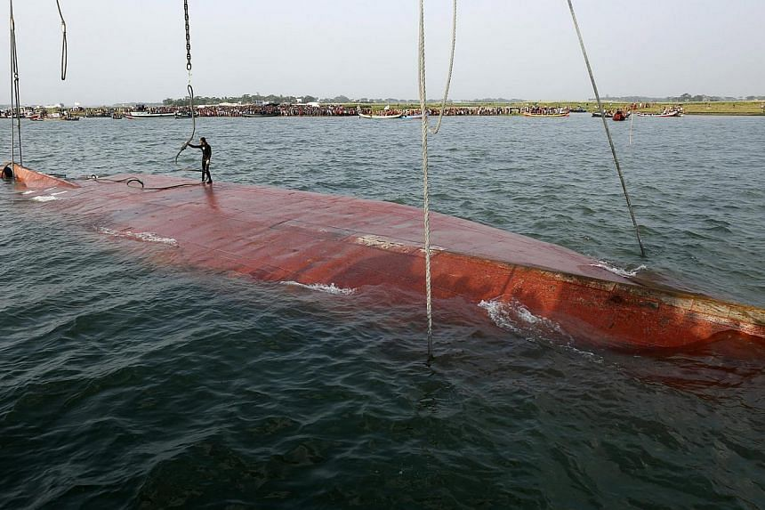 A diver of the Bangladesh Navy inspects a rope tied with the uplifted sunken ferry MV Miraj 4 in the Megna River near Munshiganj, Bangladesh, on 16 May 2014. -- PHOTO: EPA