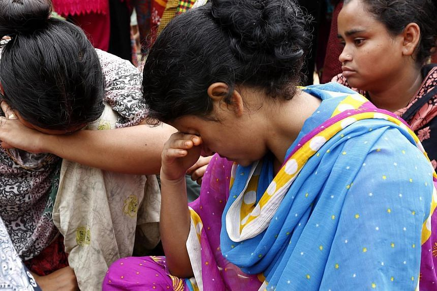 Relatives mourn as they wait for the rescue operations of the sunken ferry MV Miraj 4 in the Megna River near Munshiganj, Bangladesh, on 16 May 2014. -- PHOTO: EPA