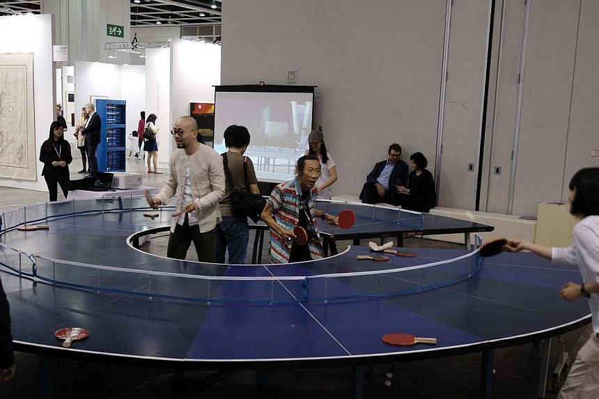 A visitor playing table tennis on an artwork titled Ping Pong Go-Round by Singapore artist Lee Wen (in colourful shirt) during the preview of Art Basel Hong Kong. -- FILE PHOTO: IPRECIATION