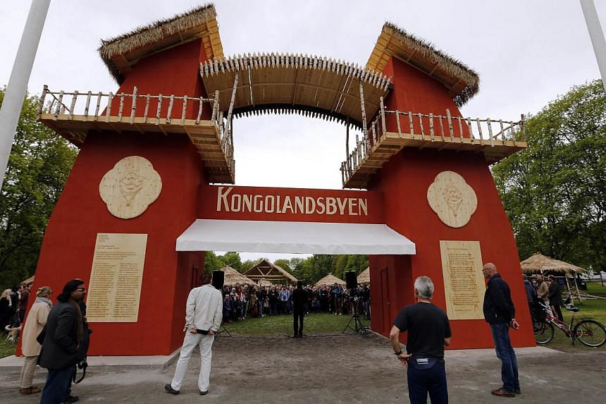 """Guests attend the opening of the """"Congo Village"""" in Oslo on May 15, 2014. Displaying 80 people in a human zoo in Oslo's most elegant park, two artists hope their """"Congo Village"""" display will help erase what they say is Norwegians' collective amnesia"""