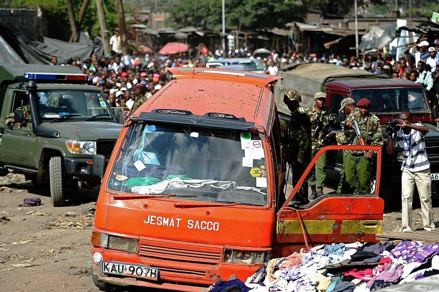 Policemen inspect the scene of an explosion in Gikomba on the outskirts of Nairobi's business district where twin blasts claimed at least ten lives on May 16, 2014. Ten people were killed and over 70 wounded when two bomb attacks in a busy market too