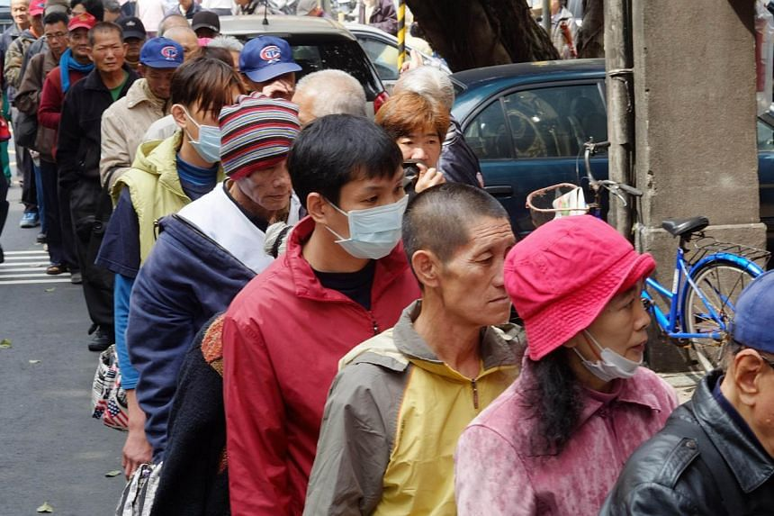 This photo taken on February 26, 2014 shows local homeless people lining up for free food outside the Grace Home Church in Taipei. In recent years the gap in Taiwan between the rich and poor has widened rapidly. -- FILE PHOTO: AFP