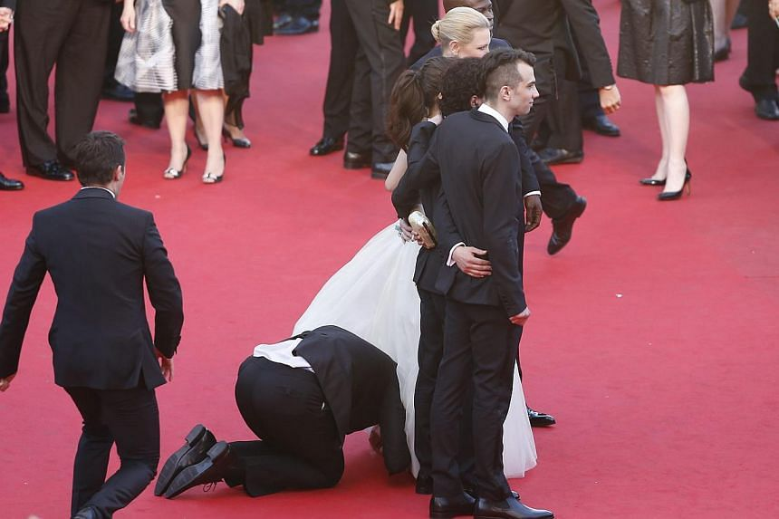 An unidentified man peeks under the dress of US actress America Ferrera as the cast arrives for the screening of How To Train Your Dragon 2 during the 67th annual Cannes Film Festival, in Cannes, France, on May 16, 2014. -- PHOTO: EPA