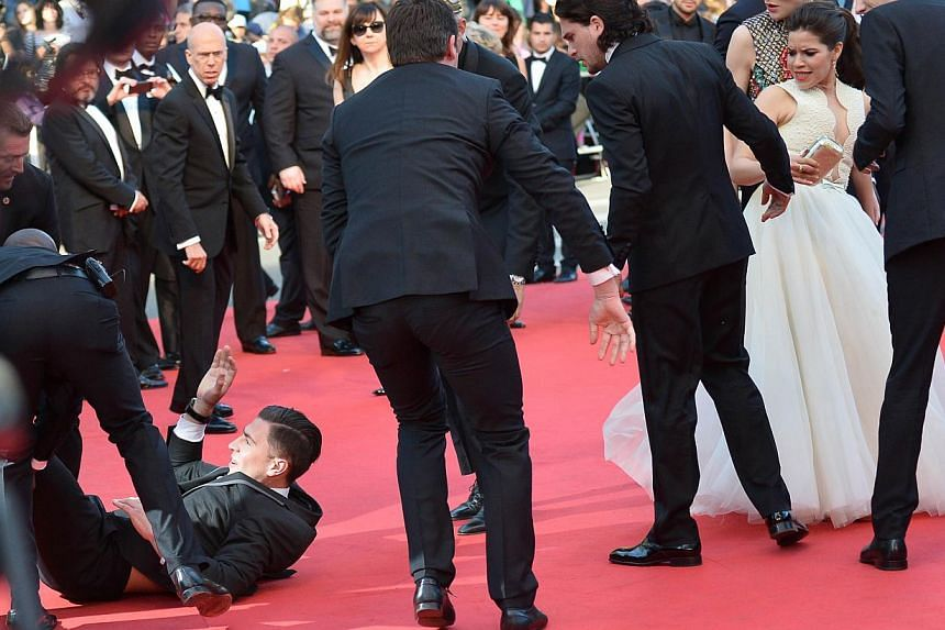 An unidentified man is dragged away by minders after he tried to slip under US actress America Ferrera's dress (right) as she arrives for the screening of the animated film How To Train Your Dragon 2 at the 67th edition of the Cannes Film Festival in