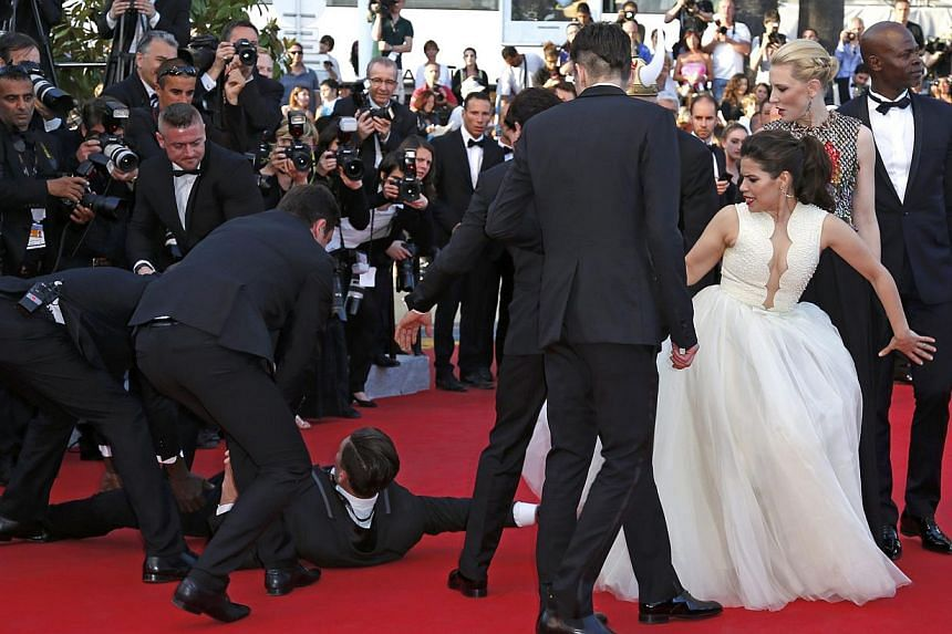 A man is arrested by security as he tries to slip under the dress of actress America Ferrera (third from right) as she poses on the red carpet arriving for the screening of the film How To Train Your Dragon 2 out of competition at the 67th Cannes Fil