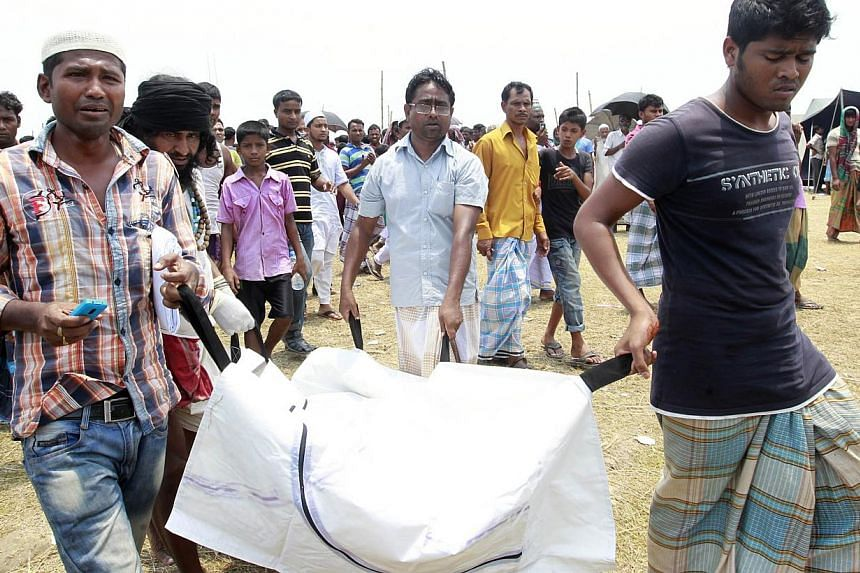 Relatives carry the body of a passenger of the capsized M.V. Miraj 4 ferry recovered from the Meghna river at Rasulpur in Munshiganj district on May 17, 2014. Anguished relatives protested a decision Saturday to stop searching for bodies of passenger