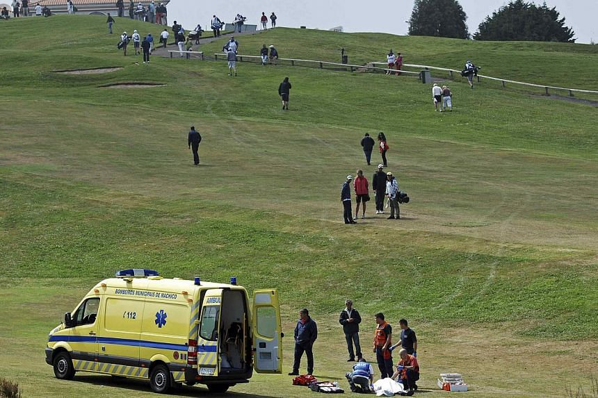 """Paramedics attend to caddie Ian McGregor as he lies on the grass during the Madeira Golf Open in Santo da Serra on May 11, 2014. The European Tour has apologised to the Caddies Association for the """"hurt and upset"""" caused following the sudden death of"""