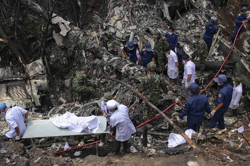 Rescue workers search an air force plane crash site near Nadee village, in Xiang Khouang province in the north of the country on May 17, 2014. A Lao military plane crashed on Saturday killing five senior officials on board including the Defence Minis
