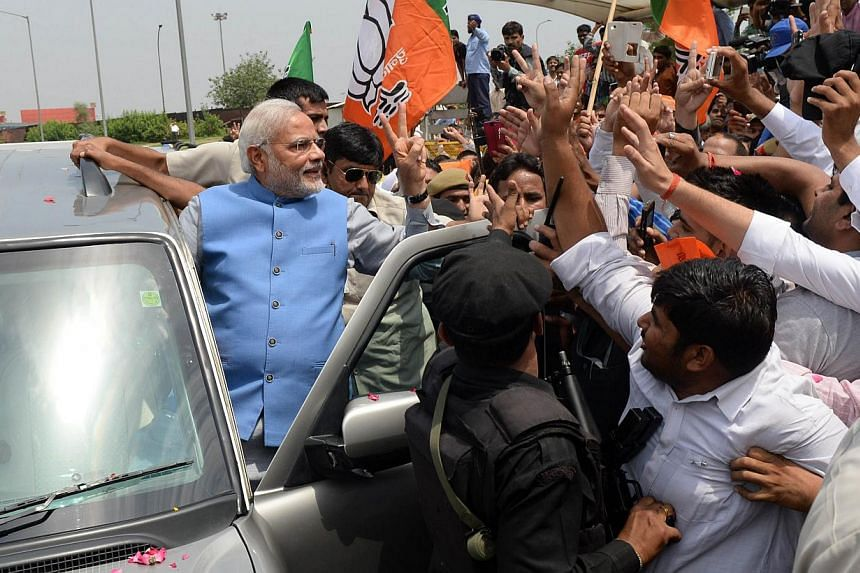 Indian prime minister-elect Narendra Modi waves to supporters as he arrives at Indira Gandhi International Airport in New Delhi on May 17 ,2014. Hundreds of flag-waving supporters mobbed Mr Modi as he arrived in New Delhi on Saturday, smiling an