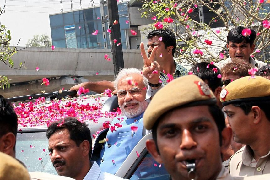 Indian prime minister-electNarendra Modi (centre) flashes a victory sign to the crowd during his road show upon his arrival in New Delhi, India, on May 17, 2014. -- PHOTO: EPA
