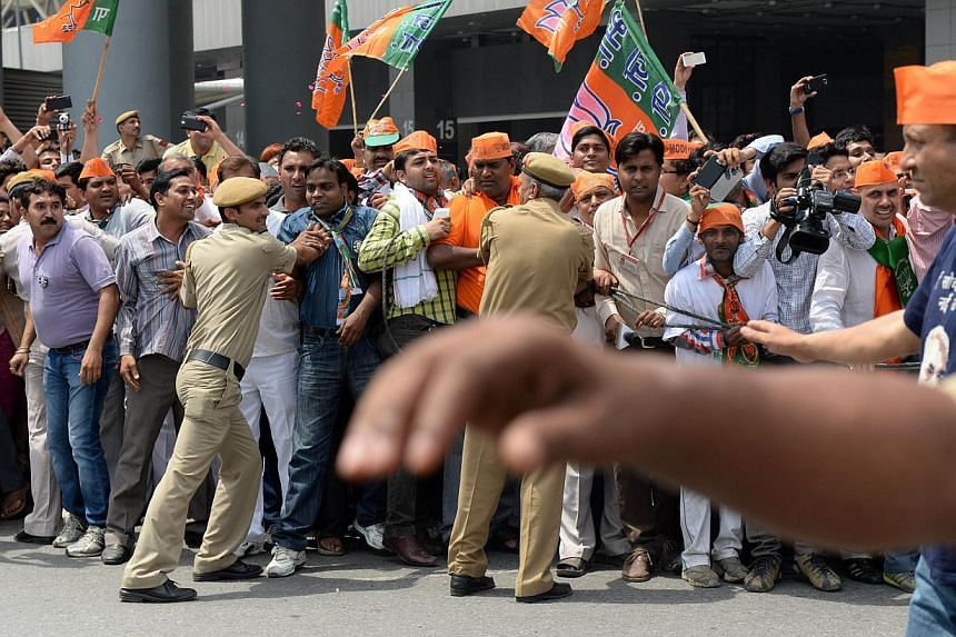 Supporters of unseen Indian prime minister-elect Narendra Modi are held back by security personnel as he arrives at Indira Gandhi International Airport in New Delhi on May 17, 2014. -- PHOTO: AFP