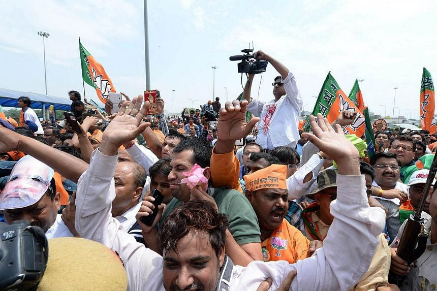 Supporters greet an unseen Indian prime minister-elect Narendra Modi as he arrives at Indira Gandhi International Airport in New Delhi on May 17, 2014. -- PHOTO: AFP