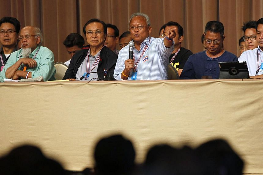 Anti-government protest leader Suthep Thaugsuban (front, third from right) speaks during a meeting with his supporters at the Government House in Bangkok on May 17, 2014. Anti-government protesters in Thailand are to stage mass rallies in coming days