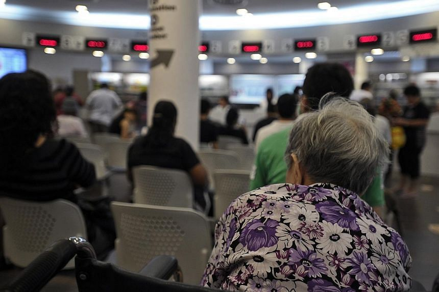 An elderly woman sits in the Pharmacy waiting area of Choa Chu Kang Polyclinic.The pioneer generation will receive more help with their outpatient healthcare needs than the poor now get. -- ST FILE PHOTO :JOSEPH NAIR