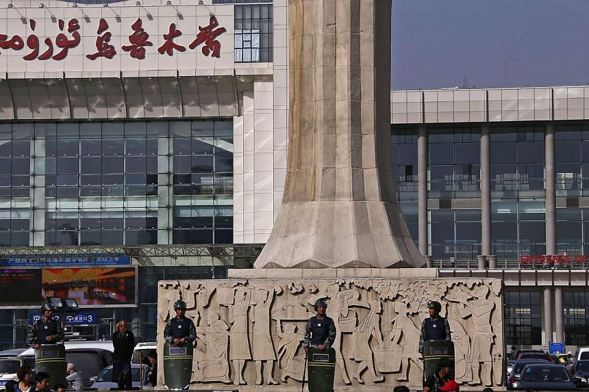 Armed police guard at the entrance of the South Railway Station, where three people were killed and 79 wounded in Wednesday's bomb and knife attack, in Urumqi, Xinjiang Uighur Autonomous region, on May 2, 2014.Chinese police have arrested seven