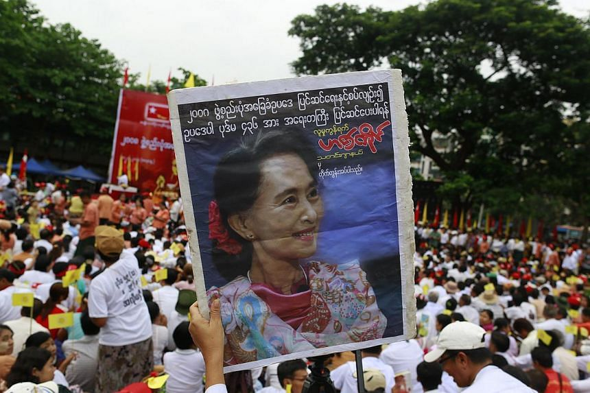 Supporter hold a portrait of Myanmar's pro-democracy leader Aung San Suu Kyi as she delivers a speech calling for the amendment of the 2008 Constitution at a rally in Boseinman Stadium in Yangon, May 17, 2014. -- PHOTO : REUTERS