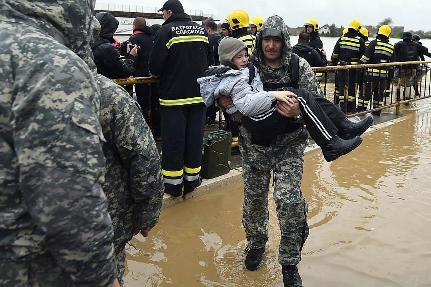 A Serbian emergency response worker carries a child as he and others evacuate people from their flooded homes in the town of Obrenovac, 40km west of Belgrade, on May 16, 2014. Emergency services pulled seven dead bodies from flooded homes in Bos