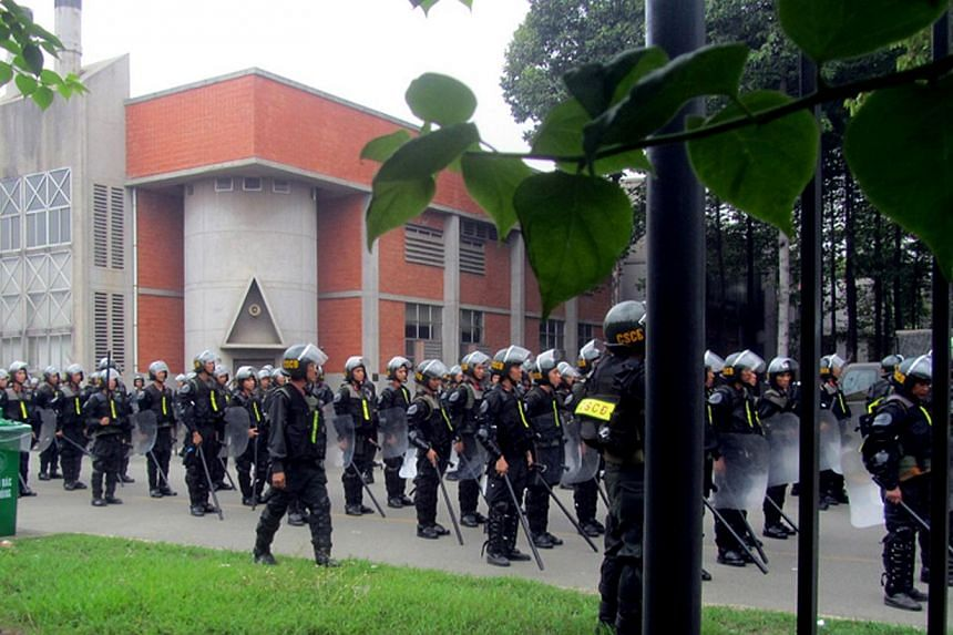 Vietnamese police officers standing guard at a Taiwanese sport shoe factory in Binh Duong as anti-China protesters set more than a dozen factories on fire in Vietnam, according to state media, in an escalating backlash against Beijing's deployment of