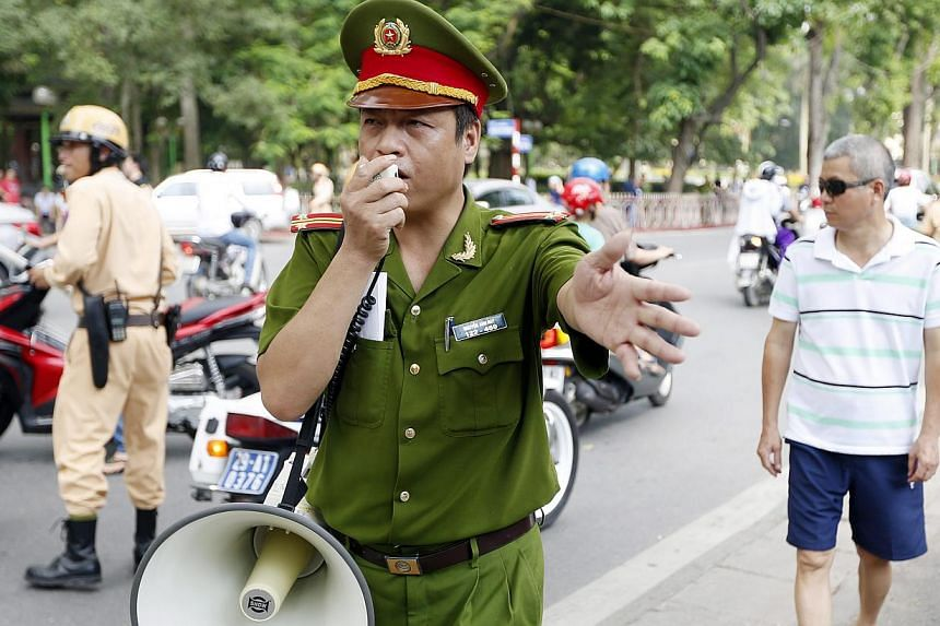 Policemen try to disperse people protesting near the Embassy of China, in Hanoi, Vietnam, on May 18, 2014. -- PHOTO: EPA