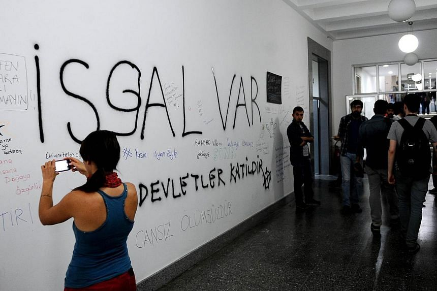 A girl takes a photo of graffiti slogans written by university students from Istanbul Technical University`s Mining Engineering Faculty on May 17, 2014, as part of a protest against the mining disaster that claimed over 300 lives. -- PHOTO: AFP
