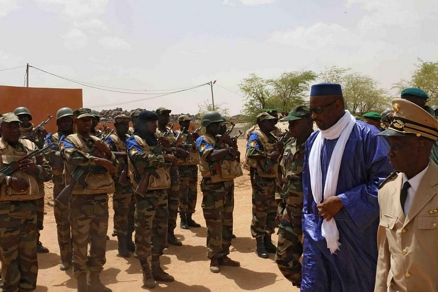 Mali's Prime minister Moussa Mara (second right) reviews troops upon his arrival at Kidal, northern Mali, on May 17, 2014, where around 30 civilians and soldiers went missing following clashes between separatist militants and the Malian army in the r