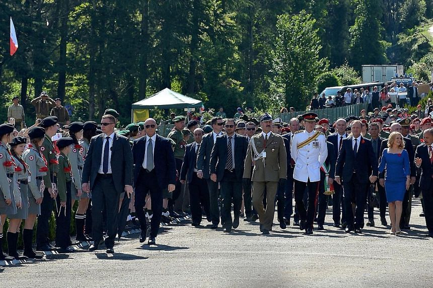 Polish Prime Minister Donald Tusk (third right) with his wife Malgorzata Tusk (second right), Britain's Prince Harry (fourth right), New Zealand Governor General Sir Jerry Mateparae (right) and Polish General Wieslaw Grudzinski (fifth right) arrive f