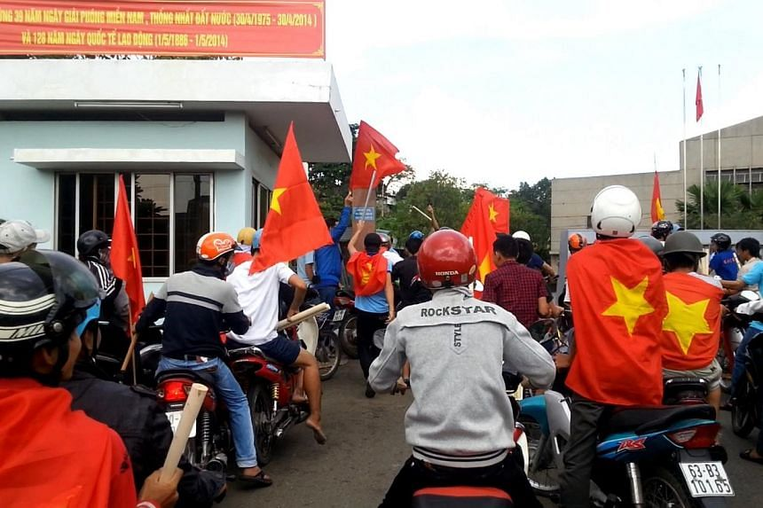 Protesters carry Vietnamese national flags as they enter a factory during an anti-China protest in Vietnam's southern Binh Duong province on May 13, 2014. China said Sunday it has suspended some plans for bilateral exchanges with Vietnam followi