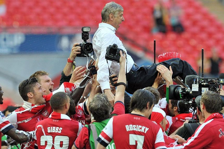 Arsenal players carry their French manager Arsene Wenger as they celebrate after winning the English FA Cup final match against Hull City at Wembly Stadium in London on May 17, 2014. -- PHOTO: AFP