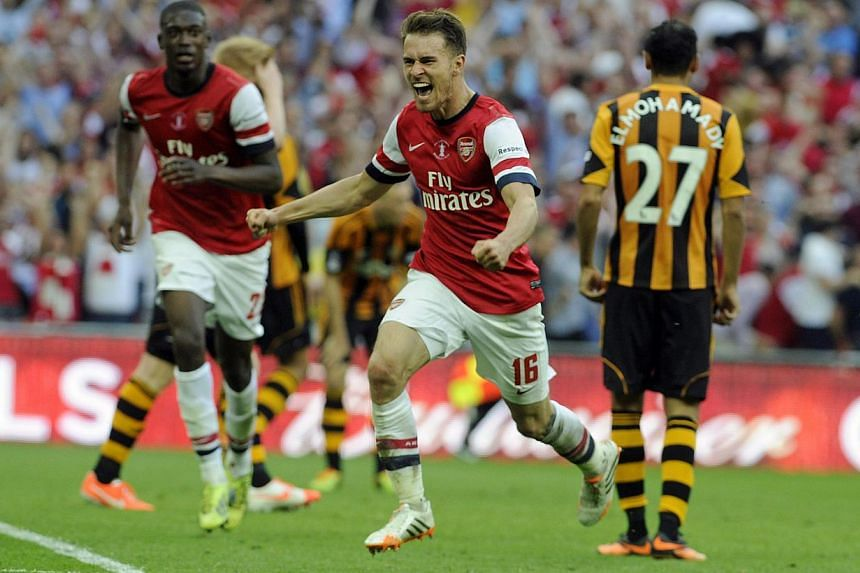 Arsenal's Aaron Ramsey (centre) celebrates scoring the winning goal during the English FA Cup final between Arsenal FC and Hull City at Wembley in London, Britain, on 17 May 2014. -- PHOTO: EPA