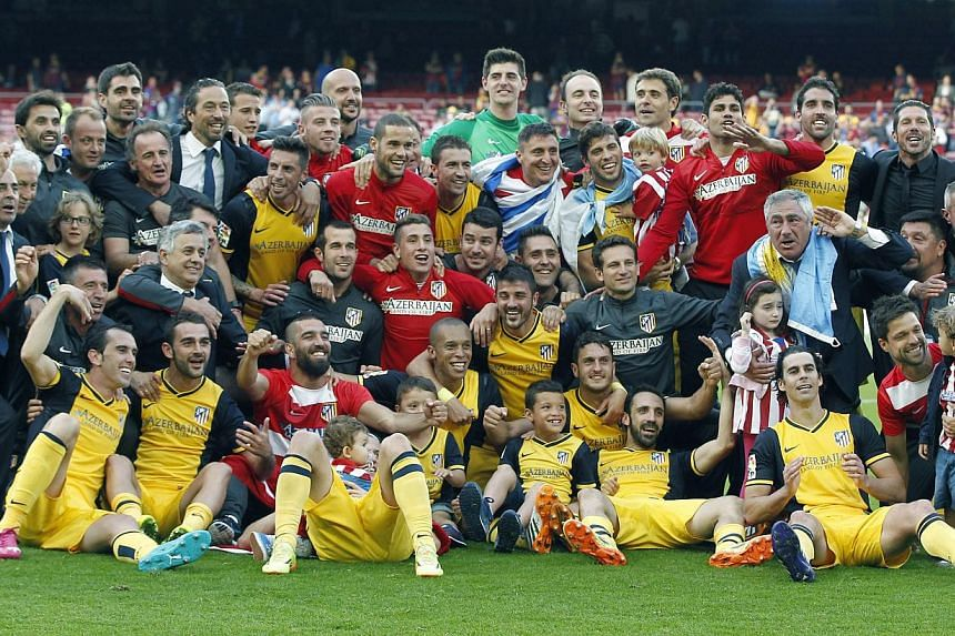 Atletico Madrid's players, coaches and managers celebrate after the Spanish Liga Primera Division soccer match between FC Barcelona and Atletico Madrid at Camp Nou stadium in Barcelona, Spain, on 17 May 2014. -- PHOTO: EPA