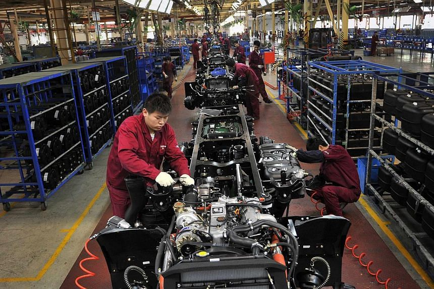 Workers install the chassis along a production line at a truck factory of Anhui Jianghuai Automobile Co. Ltd (JAC Motors) in Hefei, Anhui province on May 5, 2014. -- FILE PHOTO: REUTERS