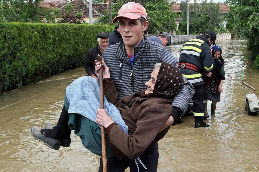 A Serbian rescuer carries an elderly woman out of her flooded house in the village of Obrez, near the central Serbian town of Varvarin, south of Belgrade on May 17, 2014. -- PHOTO: AFP