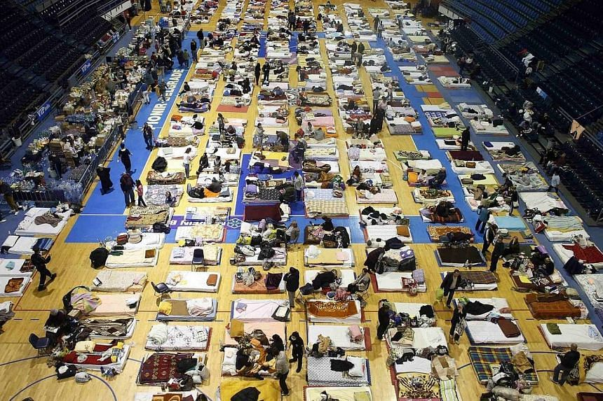 Evacuees from the Serbian town of Obrenovac are seen lying on beds in a shelter hall in Belgrade on May 18, 2014. -- PHOTO: REUTERS