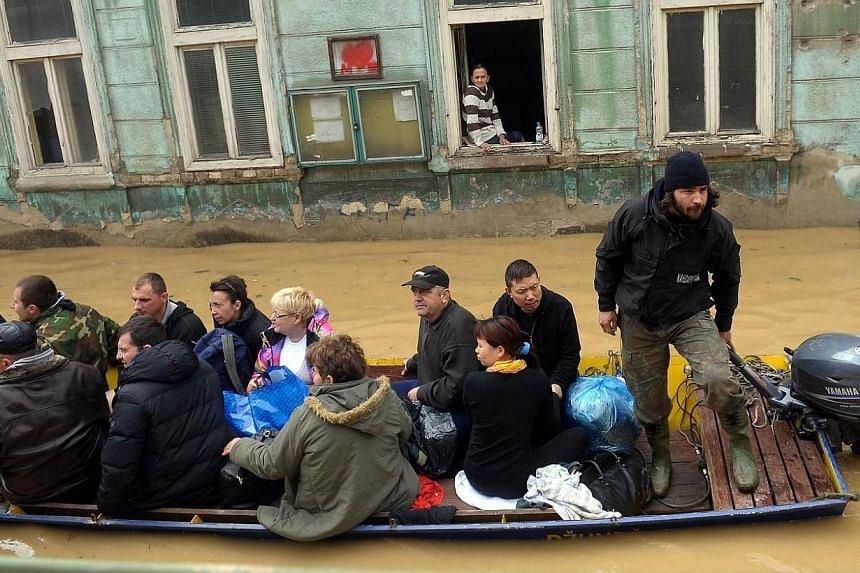 A group is evacuated by boat over flooded streets in the town of Obrenovac, 40 kilometers west of Belgrade on May 17, 2014. -- PHOTO: AFP