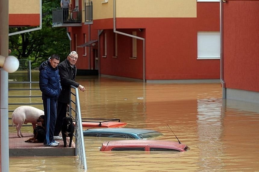 People wait for evacuation in front of their flooded house in the town of Obrenovac, 40 kilometers west of Belgrade on May 17, 2014.-- PHOTO: AFP