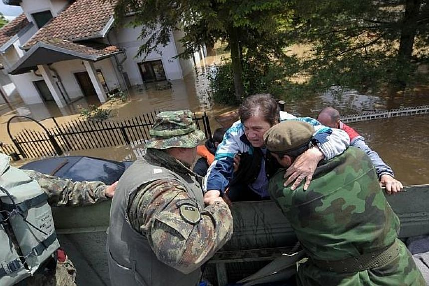 A woman is helped by rescuers after being evacuated from her flooded house in the town of Obrenovac, 40 kilometers west of Belgrade on May 17, 2014.  -- PHOTO: AFP