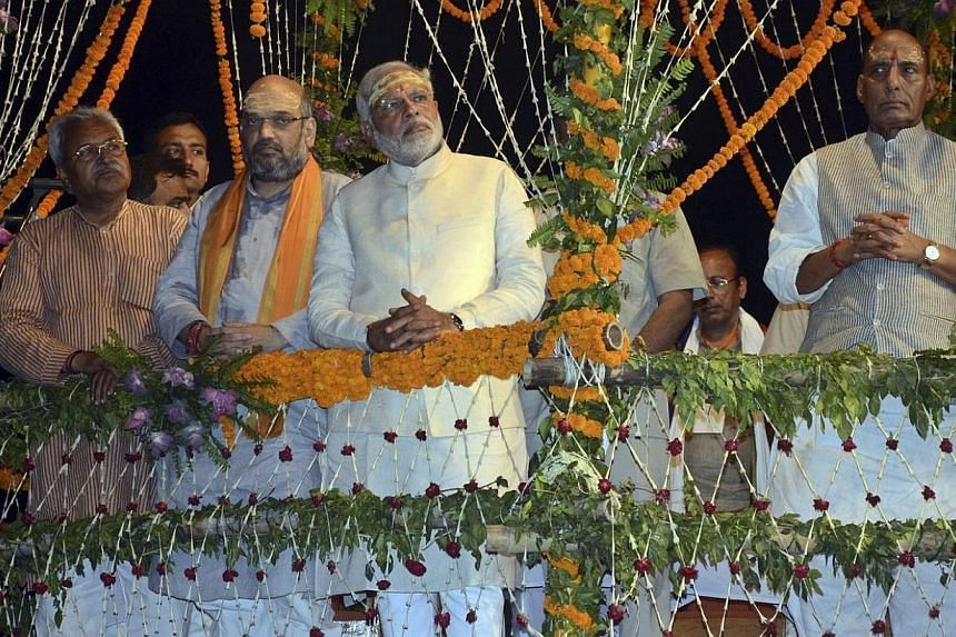 """Hindu nationalist Narendra Modi (centre), India's prime minister-elect from the Bharatiya Janata Party (BJP), watches a ritual known as """"Aarti"""" during evening prayers on the banks of river Ganges at Varanasi, in the northern Indian state of Uttar Pra"""