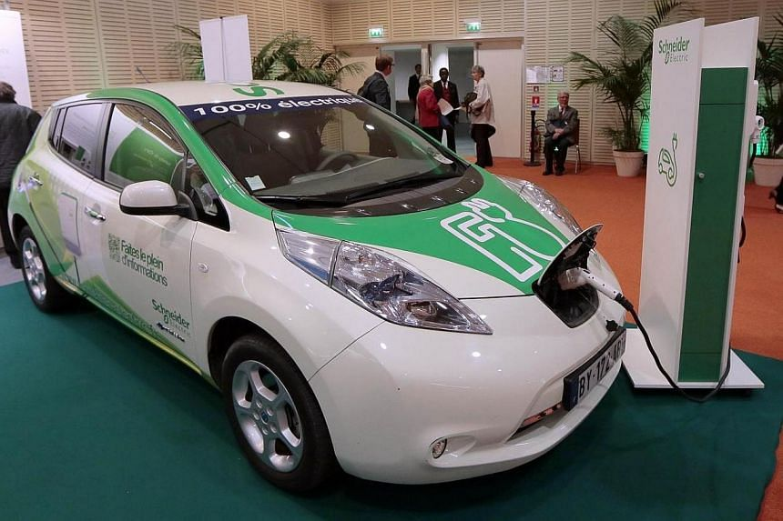 A Nissan car using the the Schneider electric technology is displayed at the entrance hall where takes place the general assembly of French electrical engineering group Schneider Electric on May 6, 2014, in Paris.Despite growing demand for elec