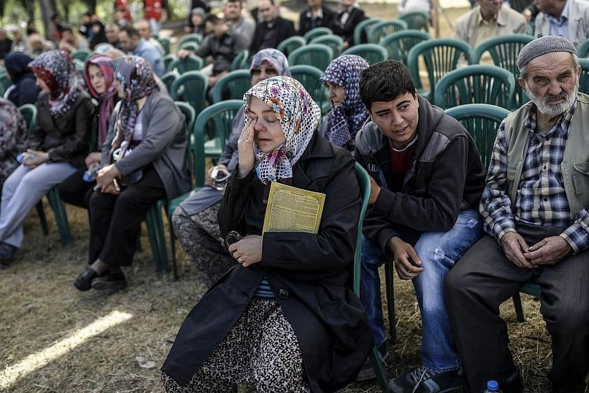 People mourn their relatives at the cemetery where some of the 301 people killed after an explosion and fire in a coal mine were buried on May 18, 2014, at Soma in Manisa. Turkish police on Sunday, May 18, 2014, detained 18 people suspected of n