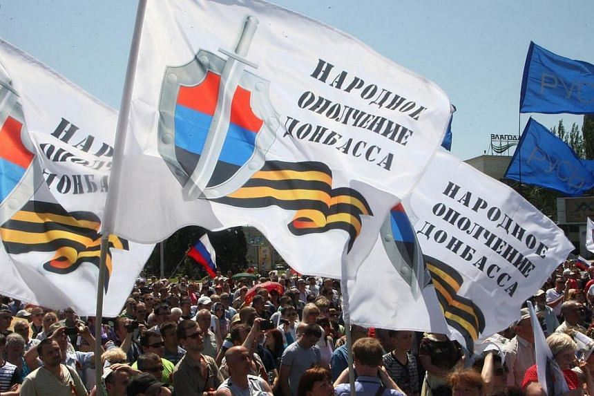 """People wave flags bearing the emblem of the so-called """"People's Republic of Donetsk"""" during a rally of pro-Russian separatists in the eastern Ukrainian city of Donetsk on May 18, 2014.Rebel leaders in eastern Ukraine launched a desperate appeal"""