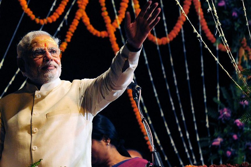 Indian prime minister-elect Narendra Modi waves to supporters after performing a religious ritual at the banks of the River Ganges in Varanasi on May 17, 2014. -- PHOTO: AFP